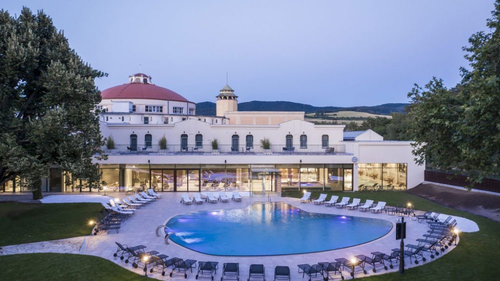 Hotel und im Vordergrund Pool und Grünanlage.