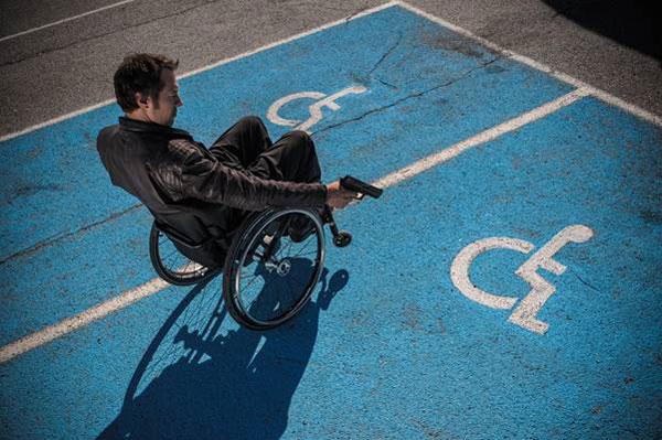 Rollstuhlfahrer steht auf Behindertenparkplatz und zielt mit Pistole auf Rollstuhlfahrersymbol